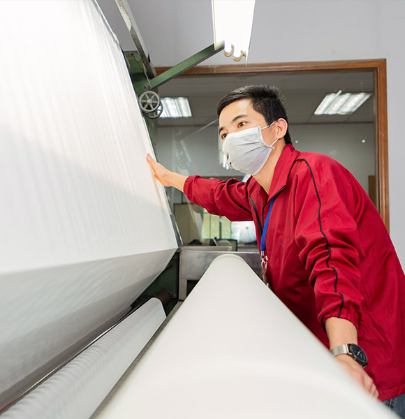 A worker is operating the fabric inspection machine